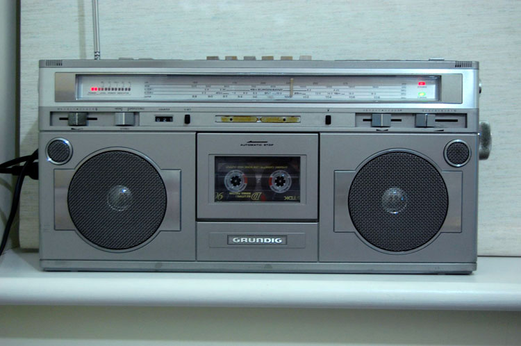 Frontal photo of the radio before any alterations were made, showing buttons on top, speakers on either side of a cassette deck, slider buttons, a radio tuning dial across the top, and sound volume indicator lights